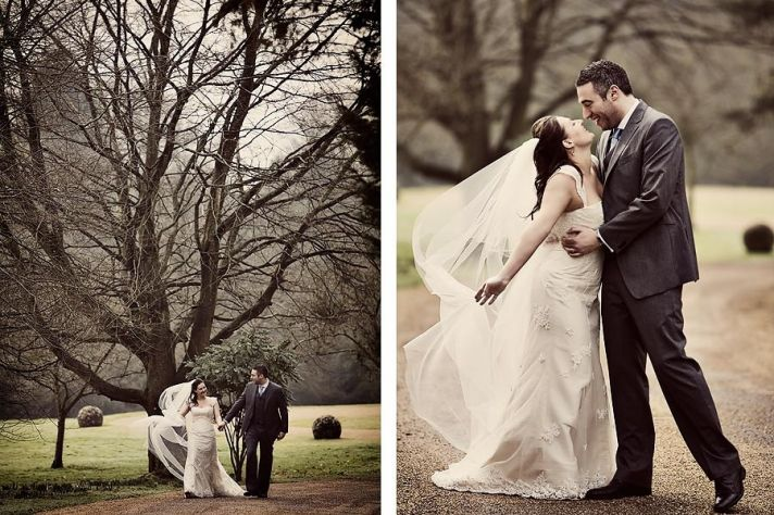 Bride and groom hold hands while walking together outside through park