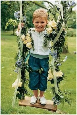 Ring bearer stands on swing decorated with ivory roses, greenery, and light blue flowers