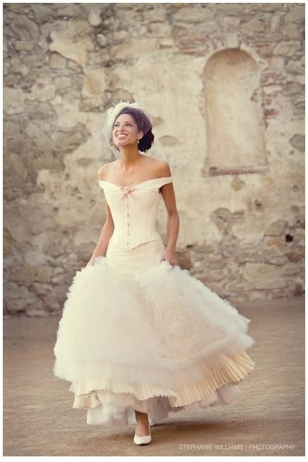 Fun and flirty off-white wedding dress, frilly skirt, pink bow, off the shoulder corset
