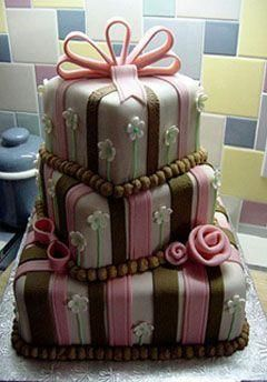 Whimsical wedding cake with pink and brown stripes, delicate white and green flowers and a pink ribb