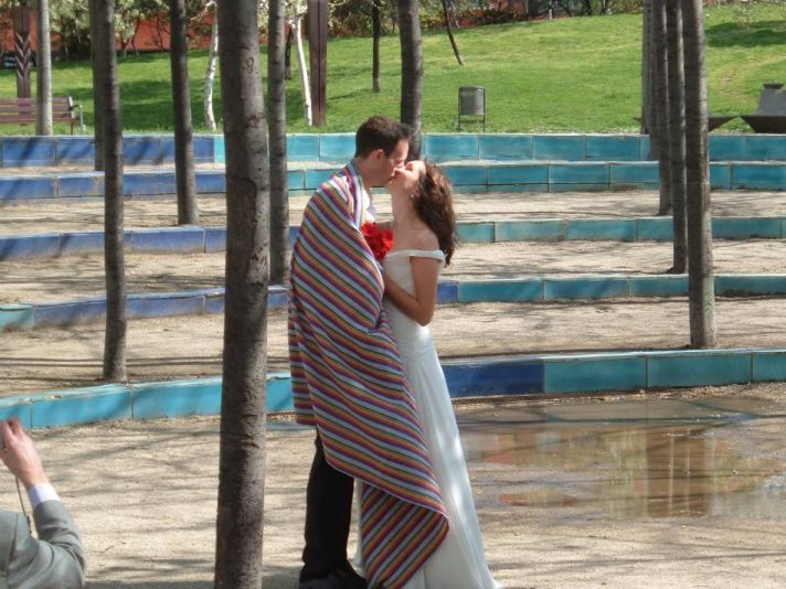 Bride and groom in outside wedding ceremony kiss while wrapped in a striped blanket. The bride holds