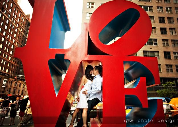 Bride and groom pose inside vibrant red LOVE monument in center of city