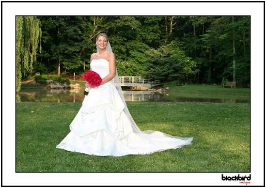 Bride in white strapless wedding dress, red floral bridal bouquet, poses outside at JMU Arboretum
