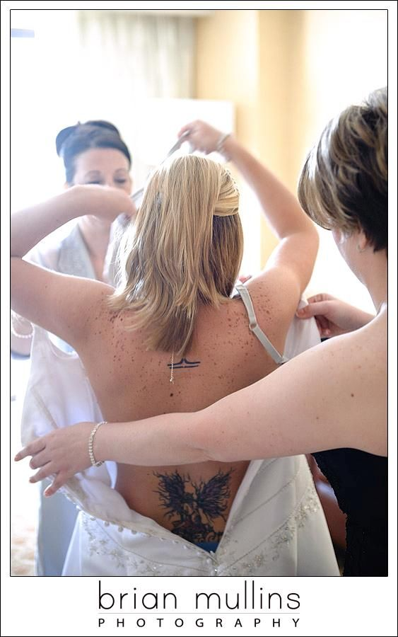 Edgy bride with tattoo puts wedding dress on before walking down the aisle with help of wedding part