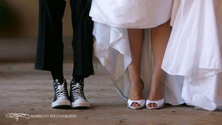 Bride in white wedding dress and white peep toe bridal shoes, groom in black converse all stars