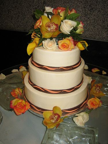 This three tiered white wedding cake with flowers in brown, orange, and yellow is perfect for a fall