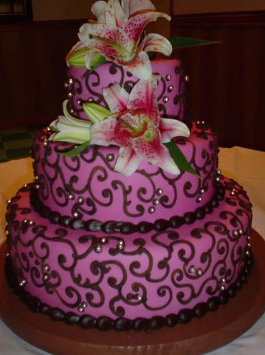 This three-tiered purple wedding cake with brown icing and pink lillies is from Bleeding Heart Baker