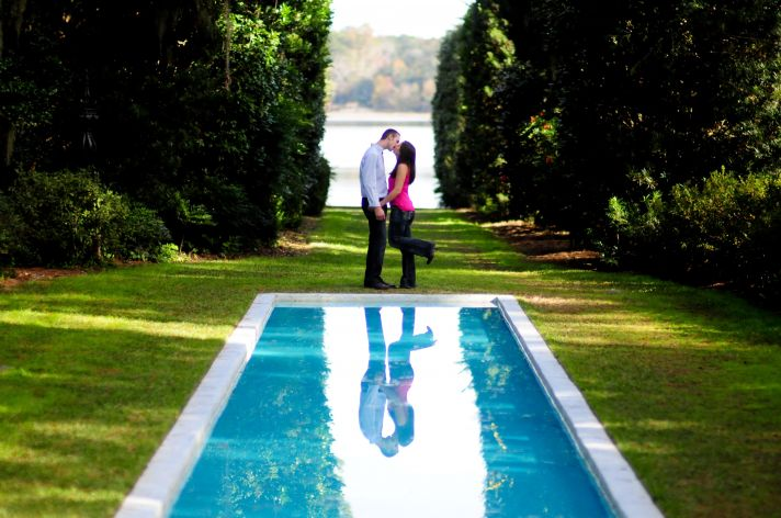 Lovely and tranquil aqua pool surrounded by lush gree grass, bride and groom kiss