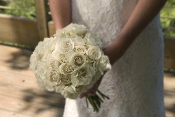 The bride's bouquet is made of white roses.