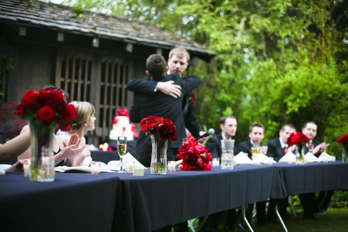 Black, white and red reception table- wedding party toasts the new couple