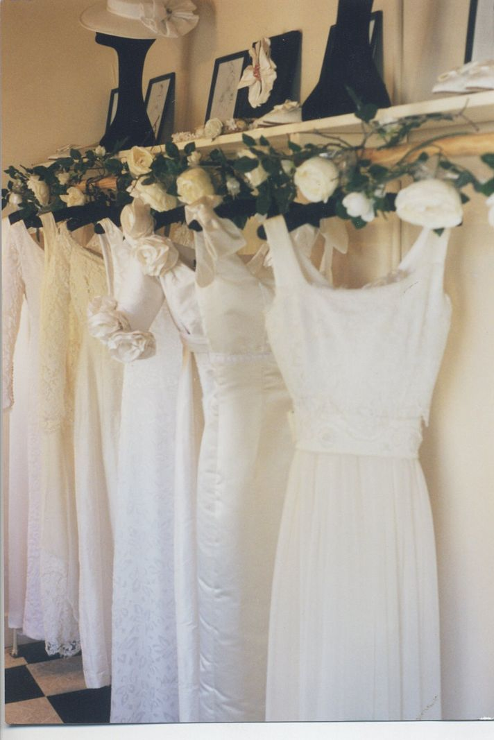 Couture wedding dresses hang in bridal shop- try on samples to find what is right for you!