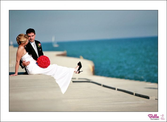 Bride in white wedding dress, black shoes and black flowered brooch, sits with groom on boardwalk of