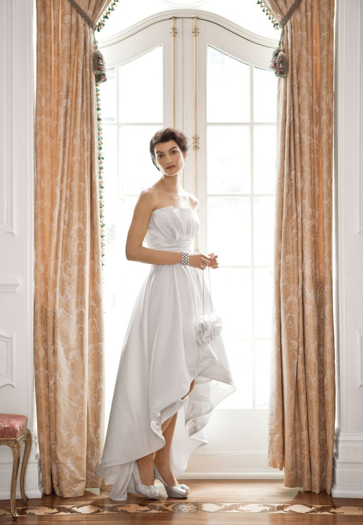 This charming destination wedding dress with a strapless neckline and an uneven front hem is from Wh
