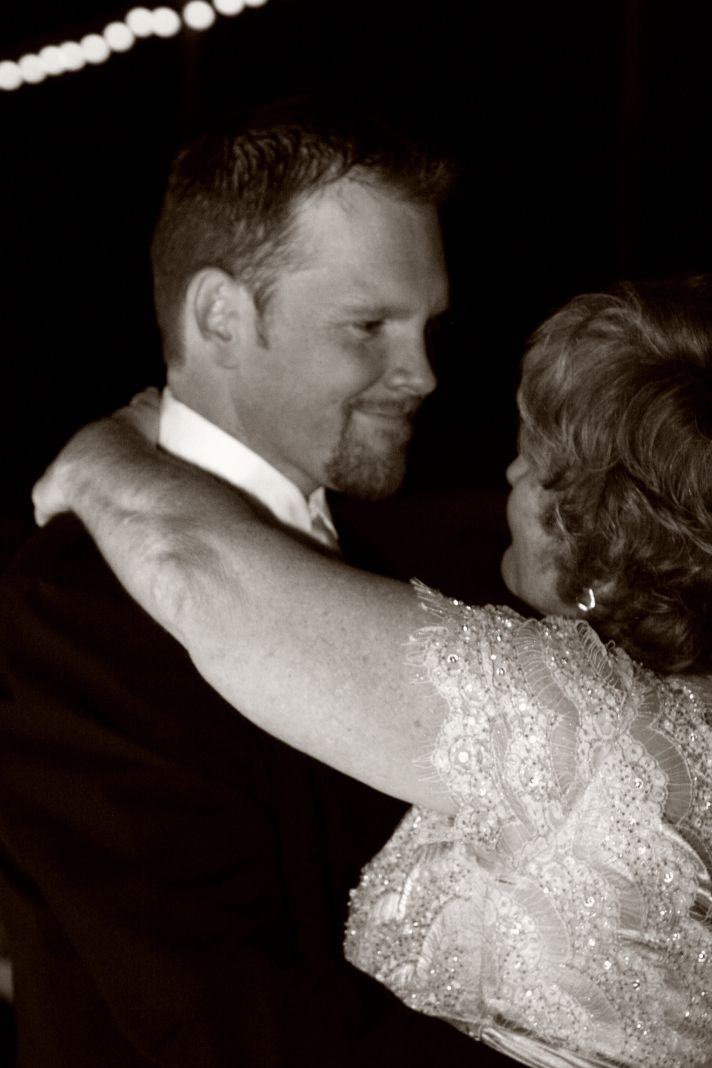 This handsome groom in his tuxedo and his mother in a lacy mother of the groom dress dance a mother