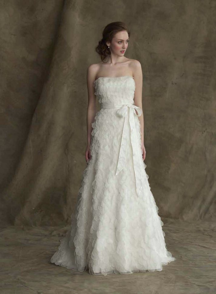 The Jacklyn wedding dress from Alyne is stunning with simple ruffles and a sash.
