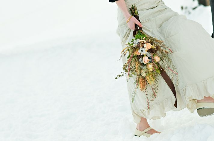 Winter wedding bride holds inventive bridal bouquet which includes paper flowers made from pages of
