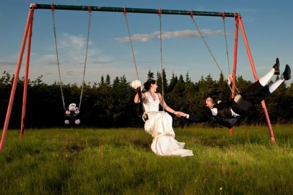 This summer bride is making the most of the season, playing outside with her groom on a swingset.