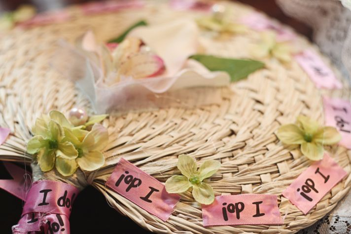 Beautiful straw fans for wedding guests adorned with pink I Do ribbon and green, pink, white flowers