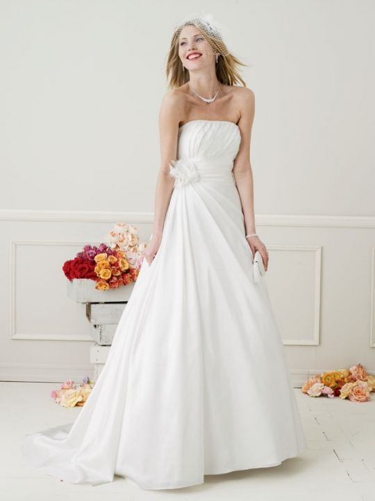 Simple and sophisticated white strapless wedding dress with full a-line skirt and floral applique at