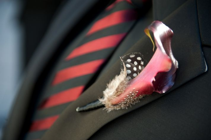Wedding detail shot- groom wears black tux, black and red tie, and statement boutonnière