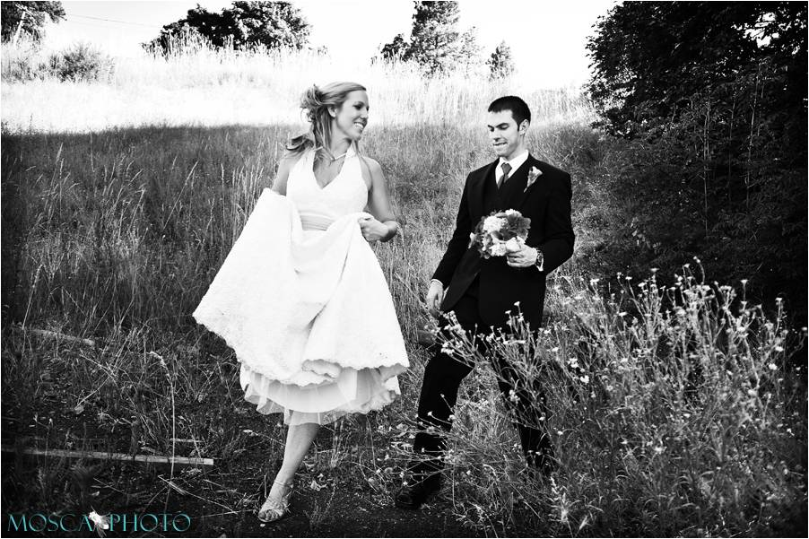 Artistic black and white wedding photo bride and groom walk through rustic