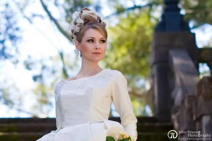 Dark blonde bride in modest long sleeved ecru toned wedding dress