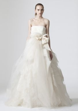 This beautiful Vera Wang wedding dress has a ball gown silhouette and a peach sash.