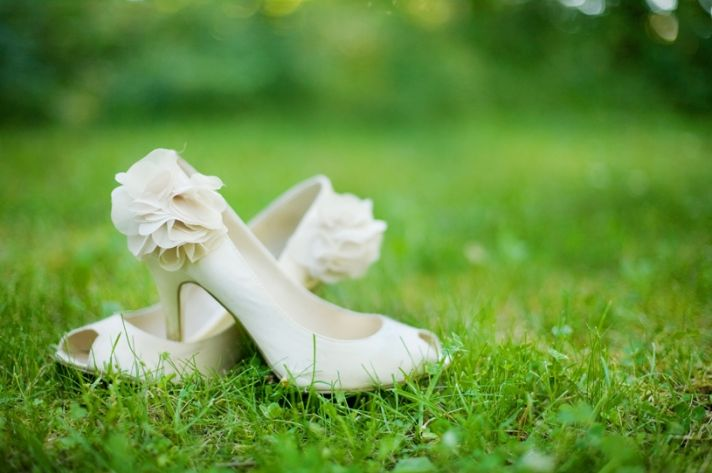 Bride's ivory peep-toe bridal heels with floral applique on heel, photographed in green grass
