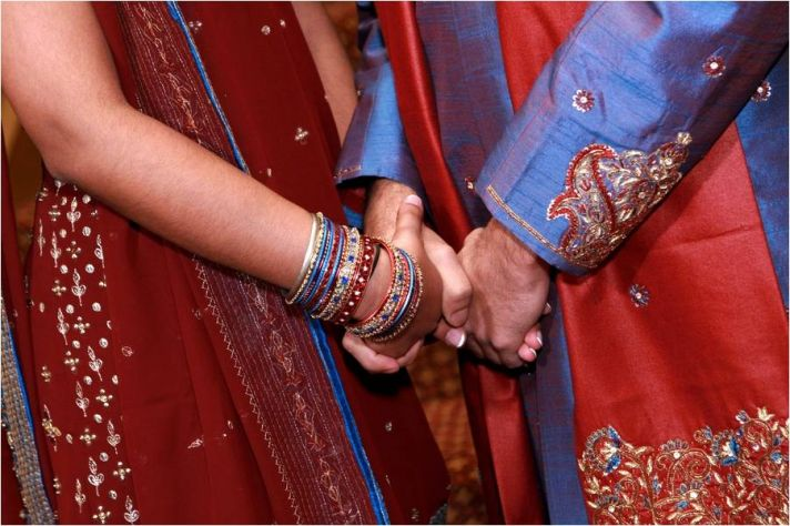 Indian bride and groom, wearing traditional colors of blue, red and gold, gold hands after saying I