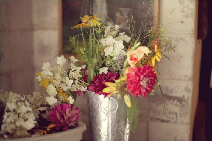 Rustic wedding flowers- yellow, ivory, red, pink wild flowers arranged in silver antique vase