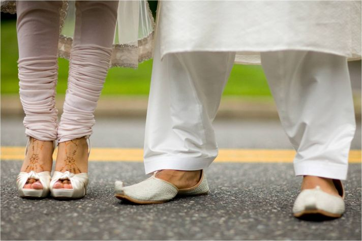 Indian bride wears traditional henna on feet, groom wears traditional shoes
