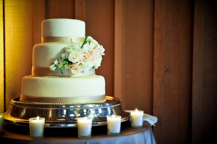 Classic three-tier ivory wedding cake adorned with pastel fresh flowers
