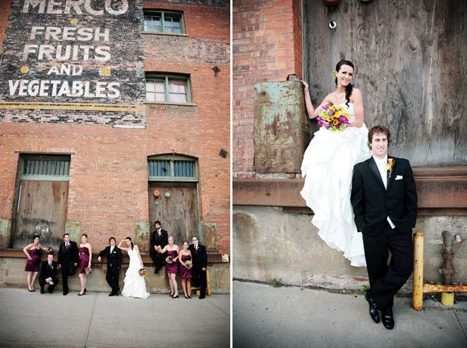 Bride and groom pose outside of old brick warehouse with entire wedding party
