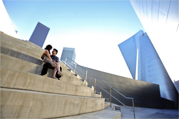 Bride and groom sit on steps outside in downtown Los Angeles with city skyline in back