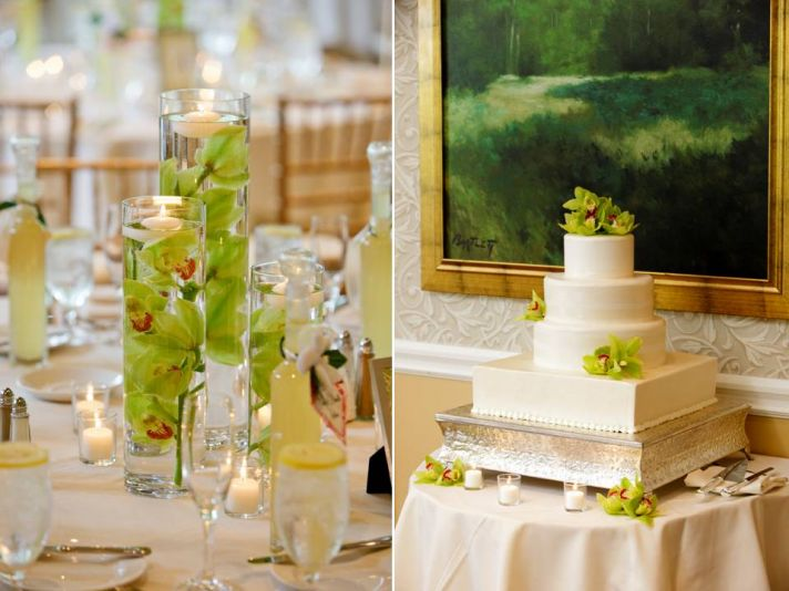 Vibrant green orchids float in clear hurricane vase; ivory wedding cake adorned with fresh orchids