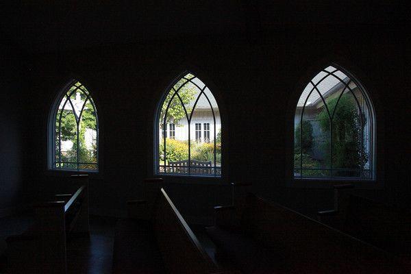 Dimly lit wedding ceremony church looks out onto lush garden