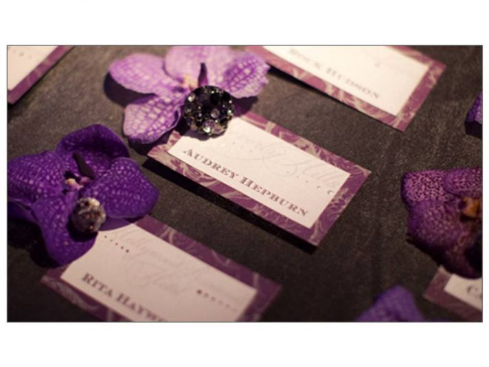 Wedding reception escort cards adorned with blinged out orchids