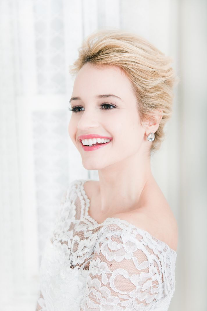 Classic swept back bridal updo with natural makeup and off-the-shoulder wedding dress