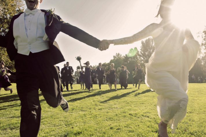 Vintage bride and groom run outside, hand in hand, at country club venue