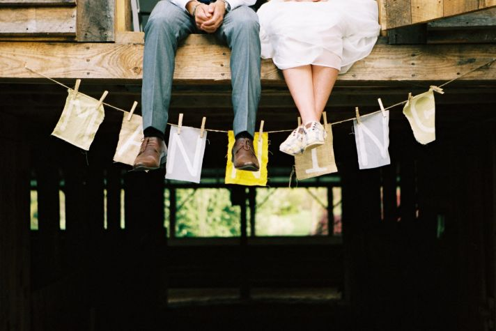 Casual bride and groom pose outside wedding venue with custom wedding monogram sign