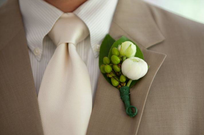 Casual grooms attire- khaki tailored suit, ivory long tie, natural boutonierre