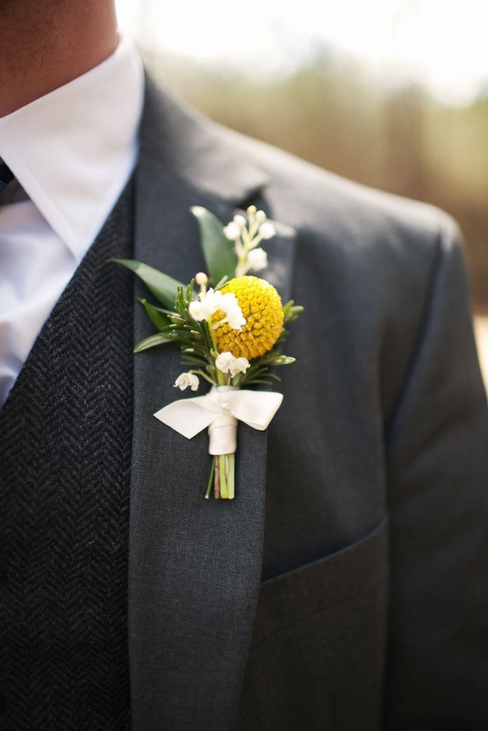 Groom wears charcoal grey suit, yellow boutonniere