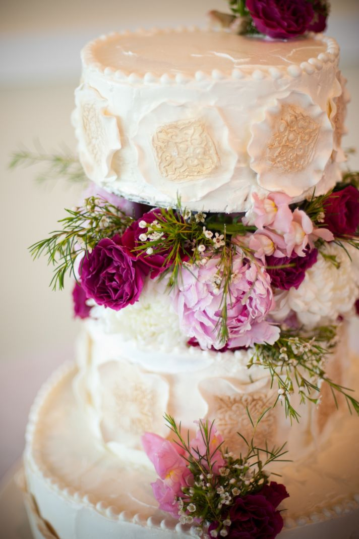 Elegant ivory wedding cake with pink wedding flowers