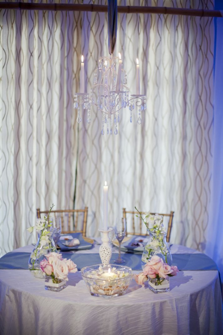 Whimsical chic seaside wedding reception decor with elegant sweetheart table