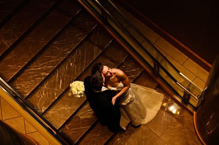 Bride and groom kiss on stairway of wedding venue