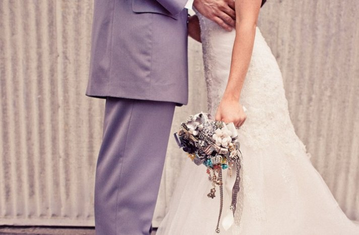 Funky bride and groom pose, bride shows off vintage brooch bouquet