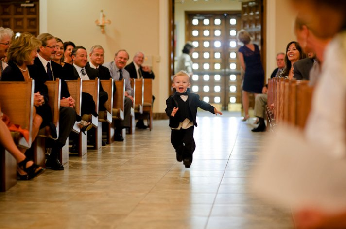 memorable wedding photos day of photography ring bearer runs down aisle
