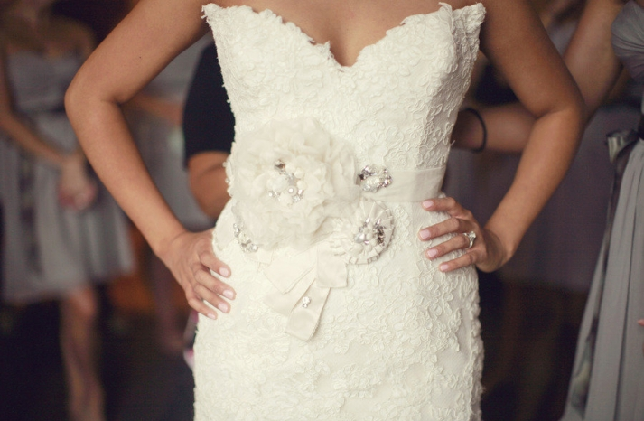 bride wears ivory lace wedding dress embellished bridal sash