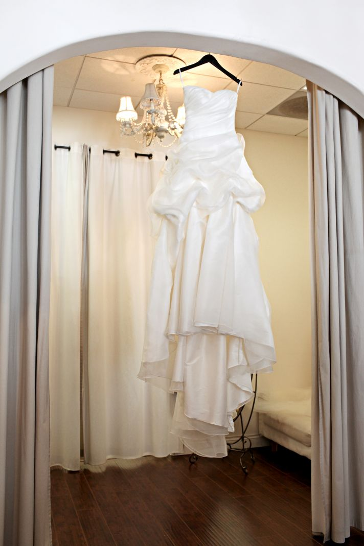 Brides Wedding Dress Hangs in Doorway