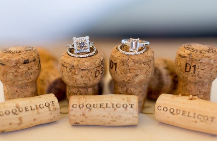 engagement rings wedding bands atop champagne corks